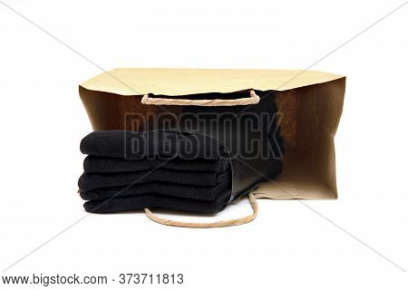 Pack Of Five Black Socks In A Brown Shopping Bag Isolated On White.