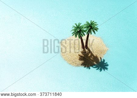 Miniature Toy Tropical Island With Palm Trees In The Ocean. Harsh Sunlight Effect, Copy Space. Creat