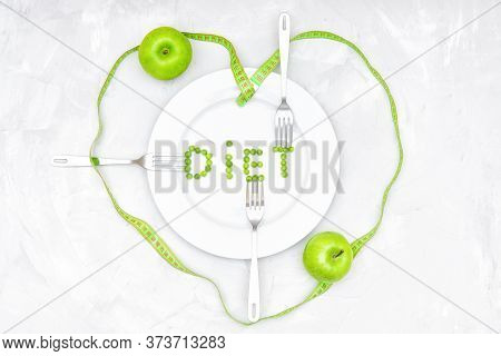 Creative Flat Lay Of The Word Diet Made Of Green Peas On White Plate, Three Forks, Two Apples And A