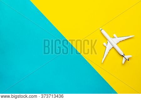 Flight Plane Travel Concept. White Toy Airplane, Aircraft On Bright Blue And Yellow. Air Sky Fly Bac