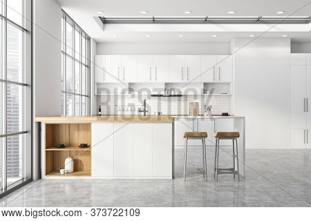 Interior Of Modern Kitchen With White And Brick Walls, Concrete Floor, White Cupboards And Counterto