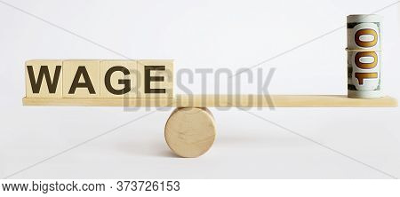 Seesaw Showing Balance Between Money And Word Wage