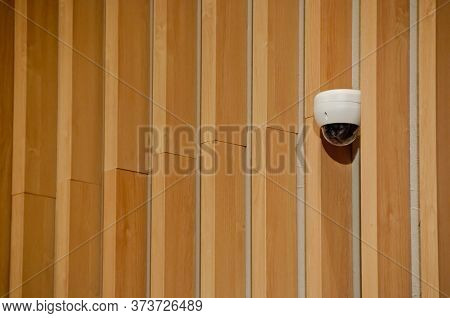 Modern White Cctv Security Camera Dome  Attached To Wooden Wall To Safeguard Wide Area