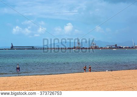 Townsville, Queensland, Australia - June 2020: A Family Paddling In The Ocean Near A Lifeguard Flag