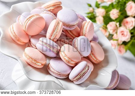 French Macarons On A Porcelain Cake Stand With Beautiful Bouquet Of Roses And Creamer At The Backgro