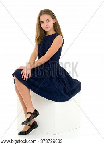 Beautiful Girl Sitting On A White Cube With Hands On Her Knees, Portrait Of A Cute Preteen Girl Look