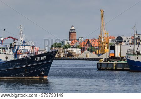 Kolobrzeg, West Pomeranian / Poland - 2020: Fishing Boats, Transshipment Quays And Lighthouse In A S