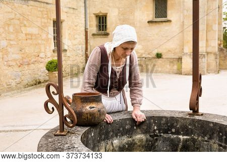 Woman in historic outfit working at an old water well of a French medieval castle