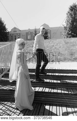 Couple Young Muslim Man And Woman Go Up On The Wooden Stairs. Muslim Tatar Wedding. Black And White