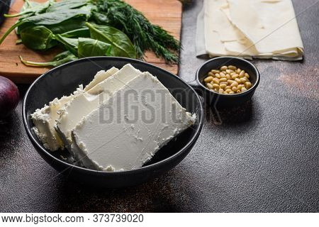 Traditional Feta Cheese In Black Bowl Side View In Front Of Ingredients