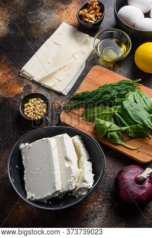 Traditional Greek Spanakopita Ingredients Filo Spinach Eggs Feta Side View On Dark Background.