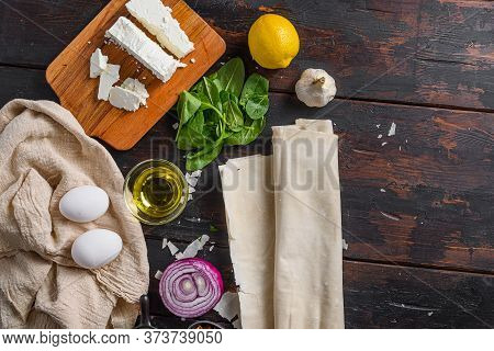 Greek Spanakopita Ingredients Filo Spinach Eggs Feta  Top View On Dark Wooden Background Space For T