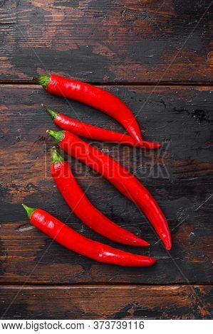 Red Hot Chili Peppers Over Old Dark Wooden Table  Top View.