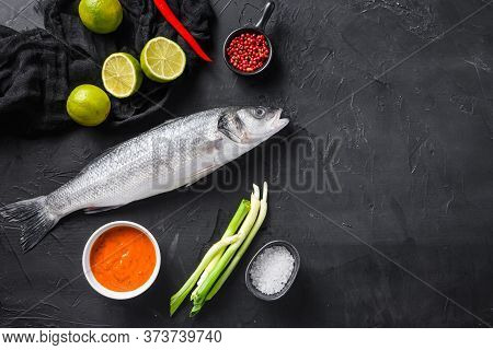 Raw Seabass With Spices And Herbs Ingredients  On Black Background Top View Space For Text.