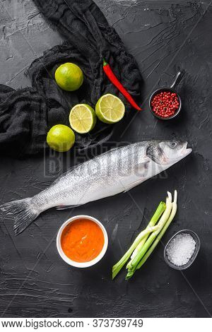 Raw Seabass With Spices And Herbs Ingredients  On Black Background Top View.