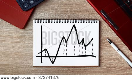 Business Growth Graph On A Sheet Of Notepad. Notepad On Desk With Laptop And A Pen.