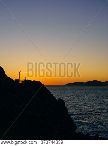 Sunset At Monteferro Lighthouse In Nigran, Galicia, Spain, With Cies Islands On Background