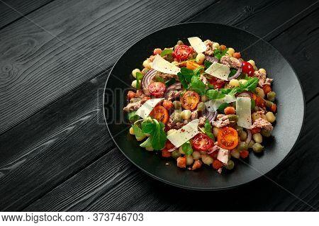 Mini Potato Gnocchi Tricolour With Tomato, Spinach, Seasonal Salad Leaves And Parmesan Cheese On Bla