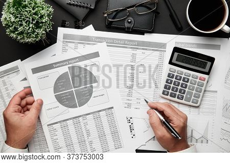 Top view of businessman's hands working with financial reports. Modern black office desk with notebook, pencil and a lot of things. Flat lay table layout.