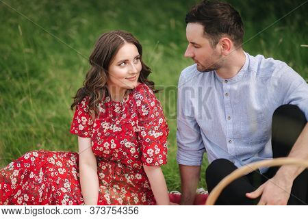 Attactive Young Woman With Handsome Man Sits Outdoors On Red Blanket