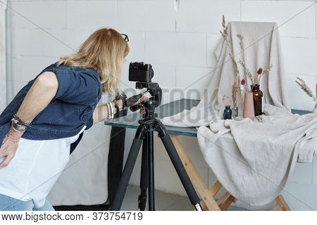 Rear view of busy creative woman using camera on tripod while photographing vase composition in studio