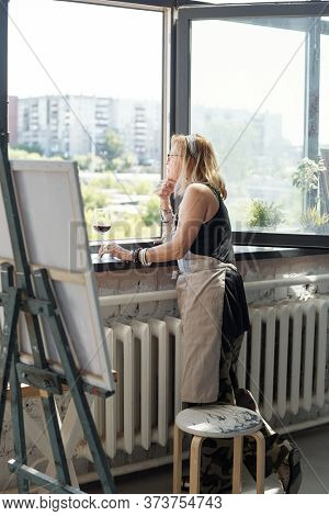 Pensive mature artist in apron contemplating cityscape through window while finding inspiration in own studio