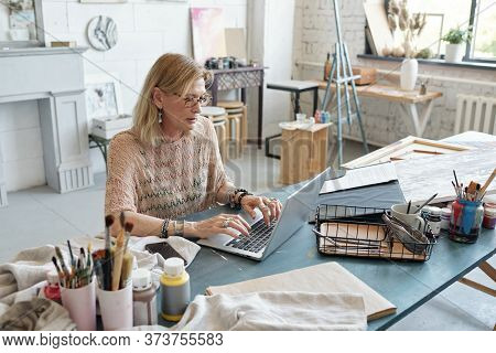 Concentrated mature artist in eyeglasses sitting at table and typing on laptop while buying consumable item for painting