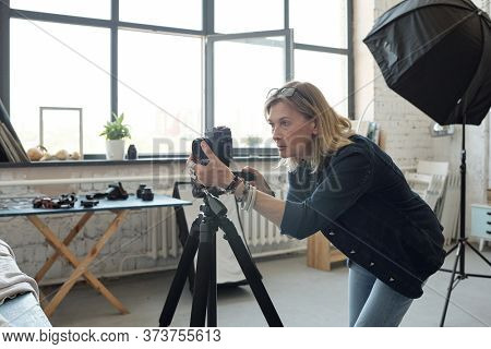 Focused mature woman with eyeglasses on head working with photographic camera in modern photo studio