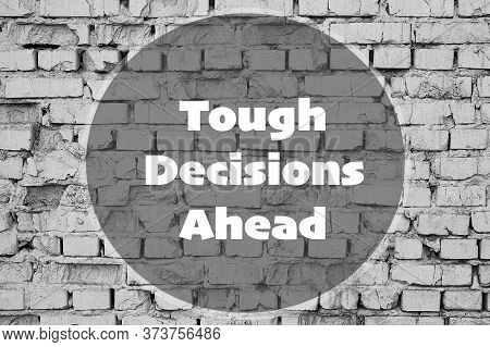 Tough Decisions Ahead - Inspirational Quote On Brick Wall Background.