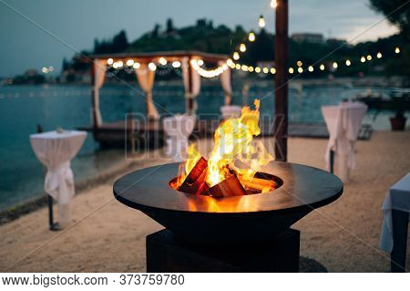 Grill With Flames Inside. Round Table-cooking Surface. On The Beach, In The Background Of The Gazebo