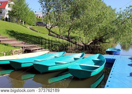 Several Boats Moored To A Small Bridge By The River