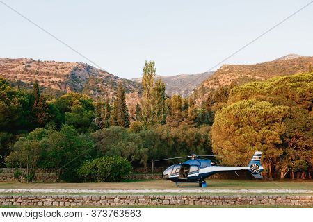 Passenger Helicopter Landed In The Park, Against The Backdrop Of The Mountains.