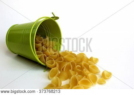 Overturned Decorative Bucket With Pasta Shell On A White Background