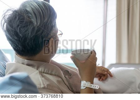 Healthcare Medical Patient Recovering Concept, Elder Asian People Sick Sitting Alone, Drink Warm Wat