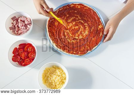 Process Of Cooking Homemade Pizza By Child. Step 2 Kid's Hands Spreads Tomato Sauce On A Dough With