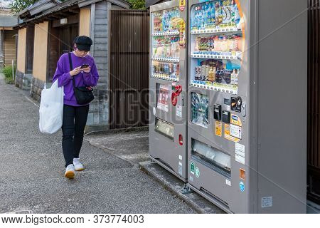 Kanazawa, Japan - September 24, 2019: A Young Japanese Woman Chating With Her Mobile While She Is Wa