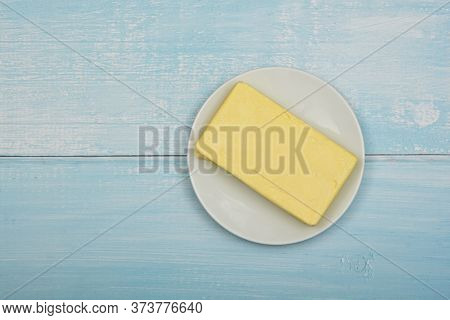 Close Up Open Fresh Yellow Hard Stick Butter In White Plate On Blue Rustick Table Surface, Elevated