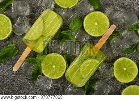 Close Up Two Frozen Fruit Juice Popsicles With Fresh Lime Slices, Green Mint Leaves And Ice Cubes On