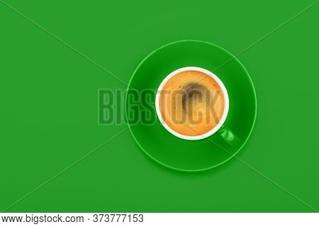 One Full Espresso Coffee Cup With Saucer Over Vivid Green Paper Background, Elevated Top View, Direc