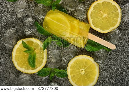 Close Up Frozen Fruit Juice Popsicle With Fresh Lemon Slices, Green Mint Leaves And Ice Cubes On Gra