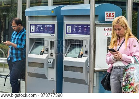 Dublin, Ireland - July 29th, 2019: Passenger Using Their Mobile Phones While Waiting The Tram Luas A
