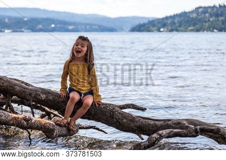 Portrait Of A Happy Little Girl Sitting On An Exposed Tree Rood In Lake Coeur D' Alene, Idaho