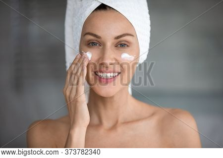 Young Woman Use Revitalizing Facial Cream In Bathroom