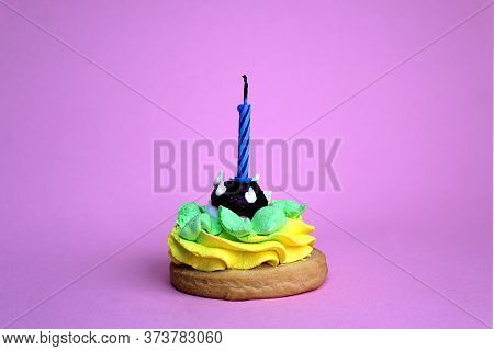 Slice Of Cake With An Extinct Candle On A Pink Background