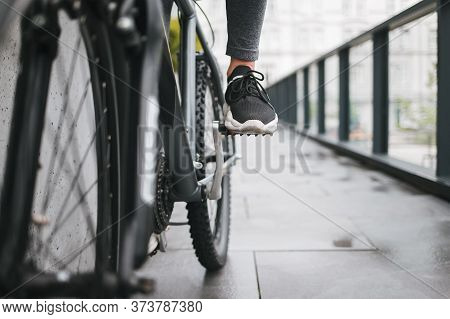 Girl's Foot On The Bicycle Pedal. Woman Rides A City On The Bike