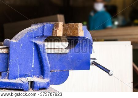 A Blue Metal Rustic Vise Closeup Over A Blur Carpentry Background.