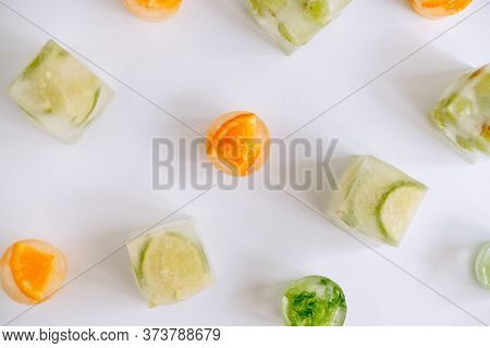 Frozen Fruits In Ice Cubes On A White Table. Top View. High Quality Photo