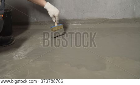 Waterproofing The Floor With A Brush And Mortar. Flooring Waterproofing. The Master Processes The Fl