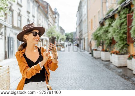 Young Stylish Woman With A Smart Phone On The Old City Street. Concept Of Happy Traveling And Summer