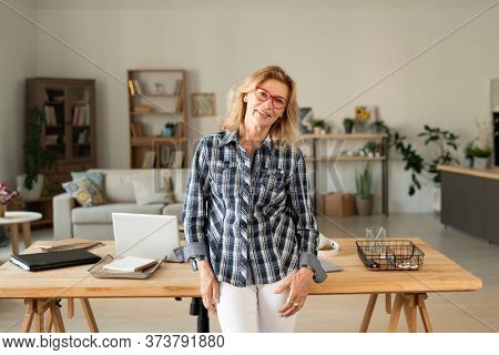 Happy casual blond female of middle age looking at you against her workplace with table, laptop, supplies and documents at home